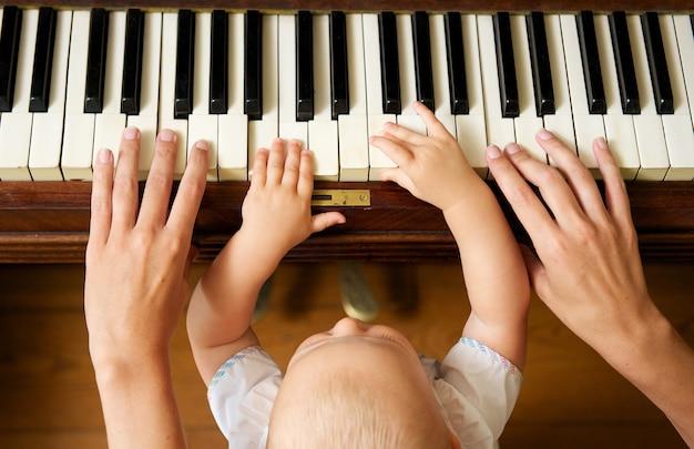 Bambino che impara a suonare il piano con la madre