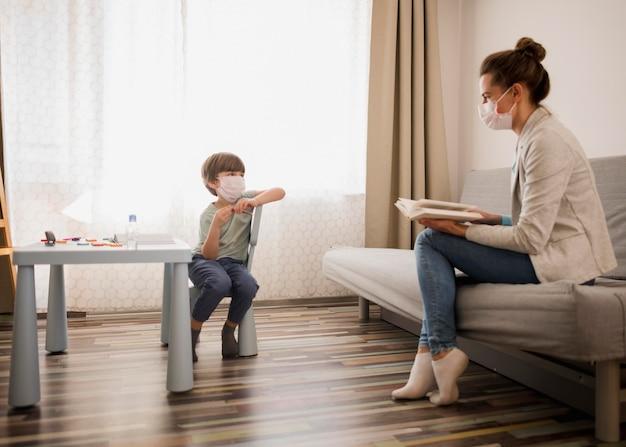 Bambino che impara dal tutor femminile a casa