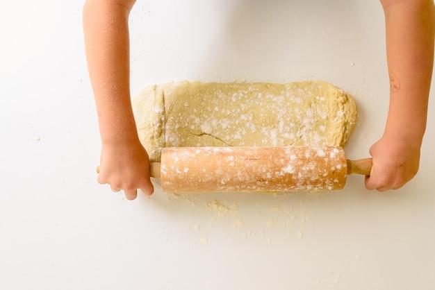 Bambino che impasta la pasta di una pizza, osservata da sopra.