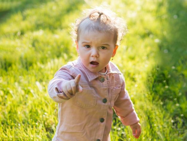Bambino che indossa abiti rosa che mostra il dito indice