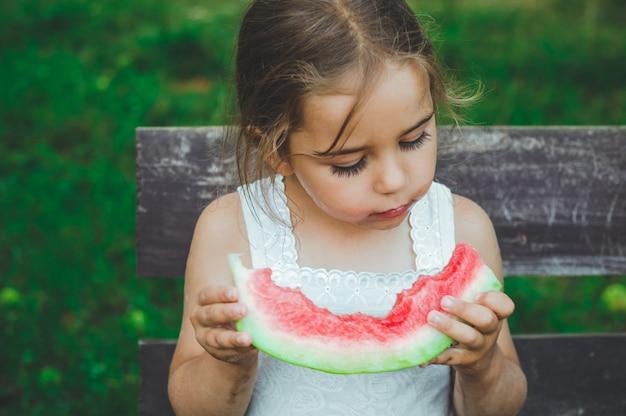 Bambino che mangia anguria in giardino. i bambini mangiano frutta all'aperto. spuntino sano per i bambini. bambina che gioca in giardino morde una fetta di anguria.