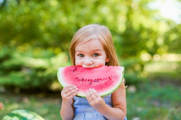 Bambino che mangia anguria nel giardino. i bambini mangiano frutta all'aperto. spuntino salutare per bambini.