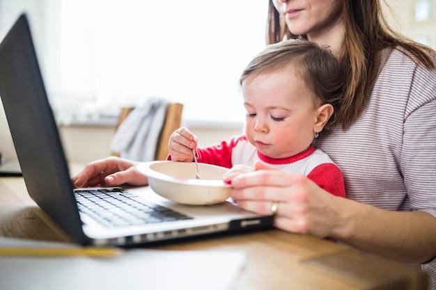 Bambino che mangia cibo mentre sua madre che lavora al computer portatile