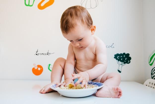Bambino che mangia da solo imparando attraverso il metodo di svezzamento guidato dal bambino
