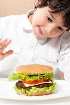 Bambino che mangia hamburger
