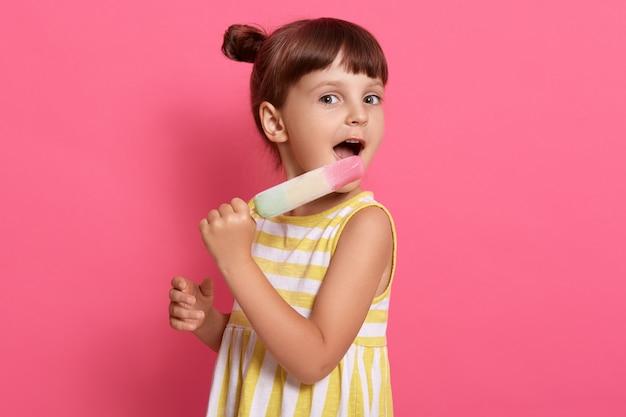 Bambino che mangia il gelato mentre posa isolato sul rosa, indossa un abito estivo con strisce bianche e gialle