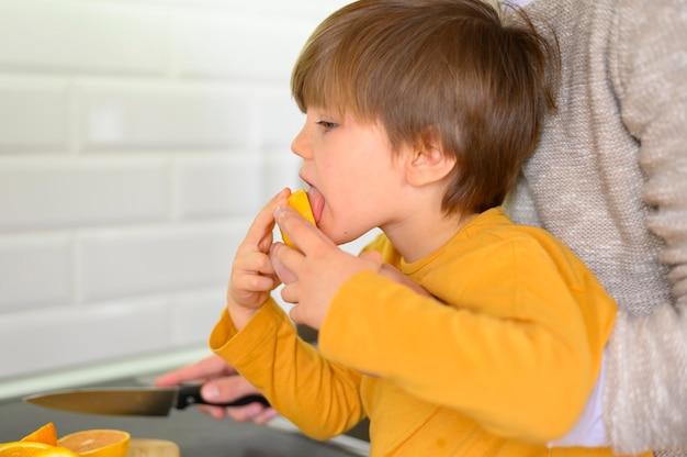 Bambino che mangia un'arancia