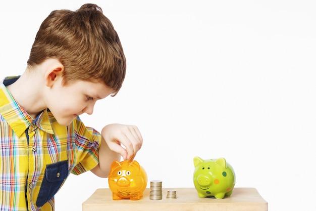 Bambino che mette moneta in una banca piggy.