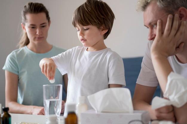 Bambino che mette una pillola in un bicchiere d'acqua