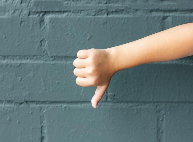Bambino che mostra i pollici in giù su priorità bassa del muro di mattoni grigio