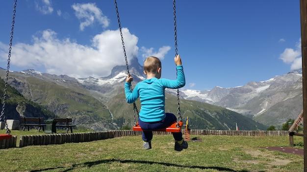 Bambino che oscilla in un parco che si affaccia sul cervino di montagna