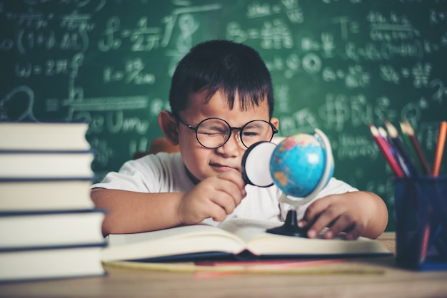 Bambino che osserva o studia il modello educativo del globo in classe.