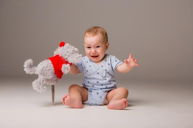 Bambino che piange isolare su uno sfondo chiaro