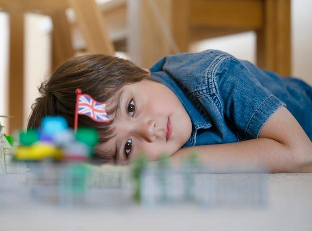 Bambino che pone sul tappeto rilassante e giocando con i soldati e il giocattolo di figurina, bambino ritagliato colpo guardando i suoi giocattoli di plastica