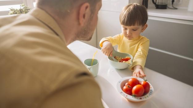 Bambino che prende i cereali dalla ciotola con il cucchiaio
