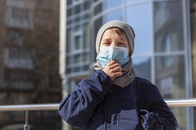 Bambino che regola la sua maschera medica fuori