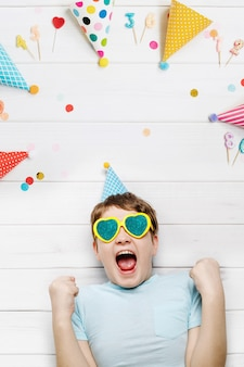 Bambino che ride che si trova sul pavimento di legno con cappelli festivi e candele su una festa di carnevale.