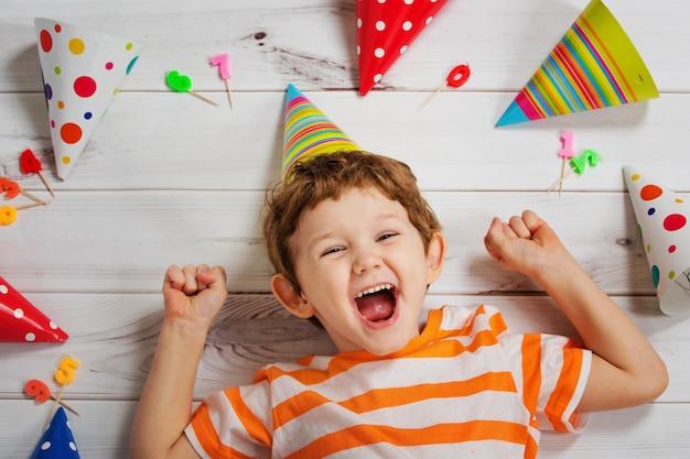Bambino che ride che si trova sul pavimento di legno con cappello di partito di carnevale.