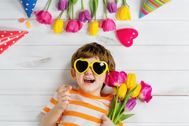 Bambino che ride che si trova sul pavimento di legno con gli occhiali per la forma del cuore sulla festa di carnevale