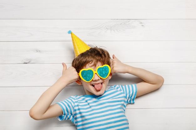 Bambino che ride felice con mostrando i pollici.