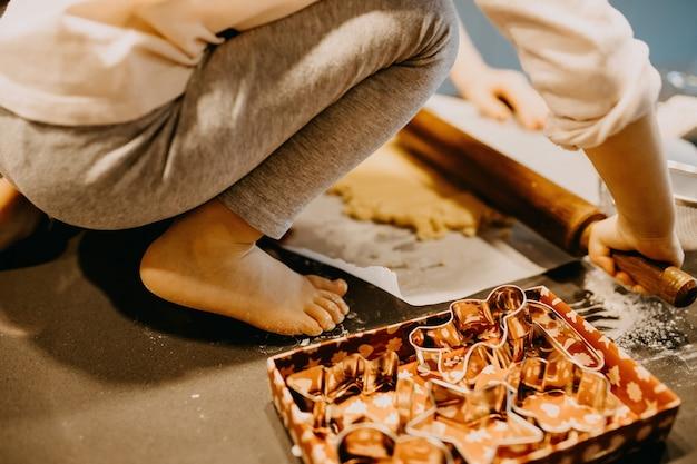 Bambino che rotola la pasta con un mattarello per i biscotti
