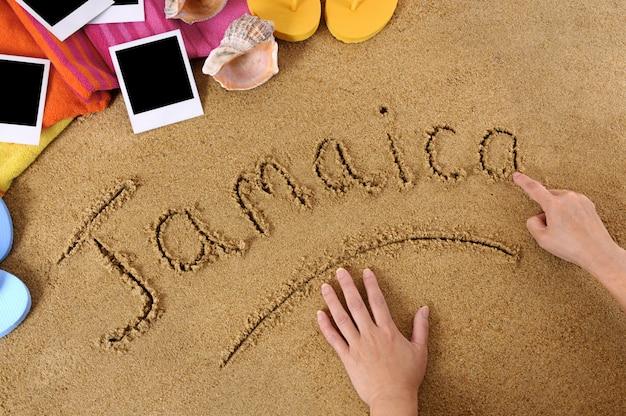 Bambino che scrive la parola giamaica nella sabbia con asciugamano, infradito e stampe fotografiche in bianco