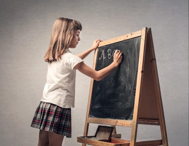 Bambino che scrive su una lavagna