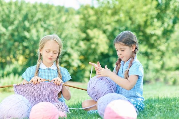Bambino che si siede sull'erba verde e che lavora a maglia maglione con gli aghi il giorno di estate.