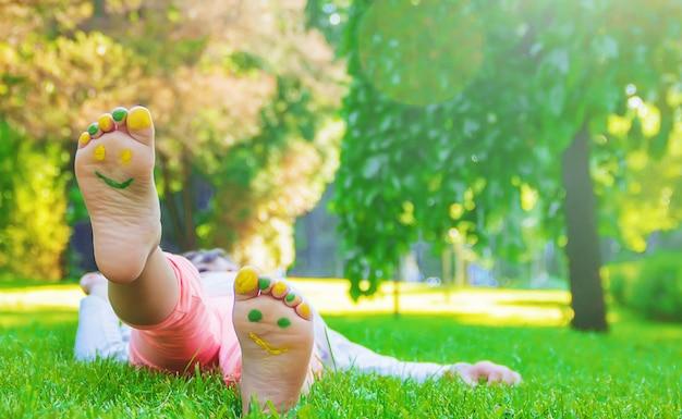 Bambino che si trova sull'erba verde. bambino divertendosi all'aperto nel parco di primavera.