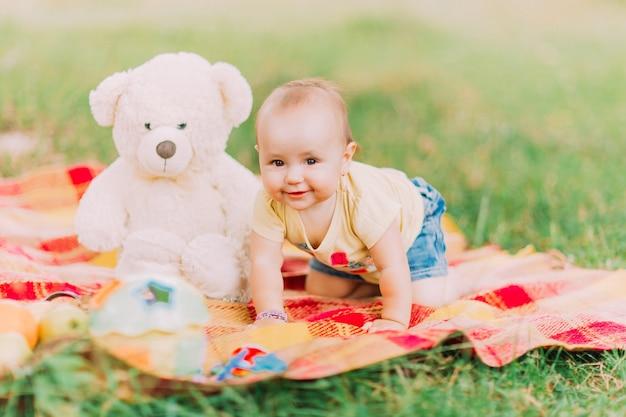 Bambino che striscia su una coperta con un orsacchiotto accanto ad essa