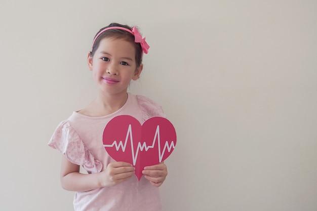 Bambino che tiene grande cuore rosso con cardiogramma