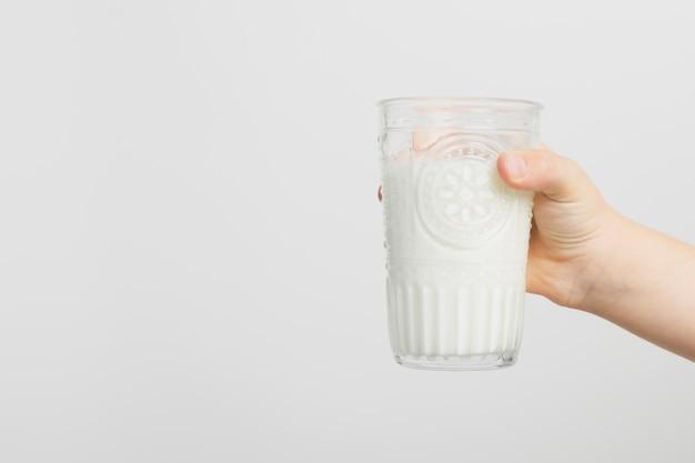 Bambino che tiene il bicchiere di latte con copia spazio