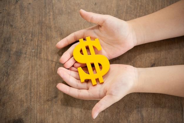 Bambino che tiene il simbolo di dollaro giallo