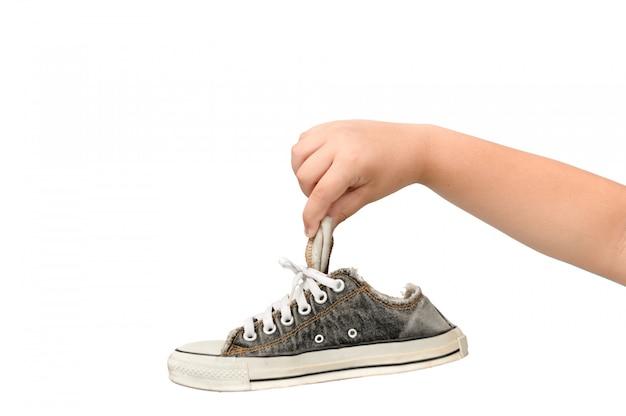 Bambino che tiene una vecchia sneaker sporca e puzzolente