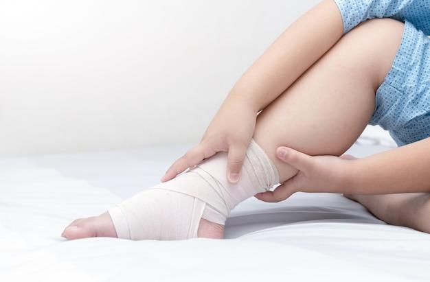 Bambino che tocca la caviglia con bendaggio elastico, gamba rotta, concetto doloroso e di assistenza sanitaria