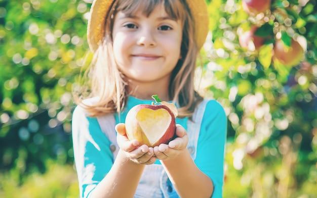 Bambino con bambino con una mela. messa a fuoco selettiva