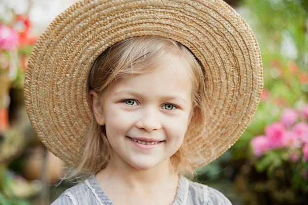 Bambino con cesto di fiori. ragazza che tiene i fiori rosa