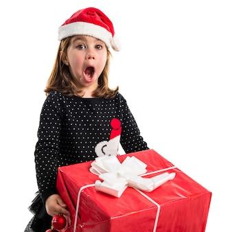 Bambino con grande regalo rosso facendo il gesto di sorpresa