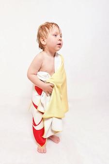 Bambino con i capelli bagnati avvolti in un telo da bagno