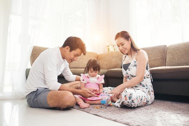 Bambino con i suoi genitori che giocano sul pavimento nel salotto