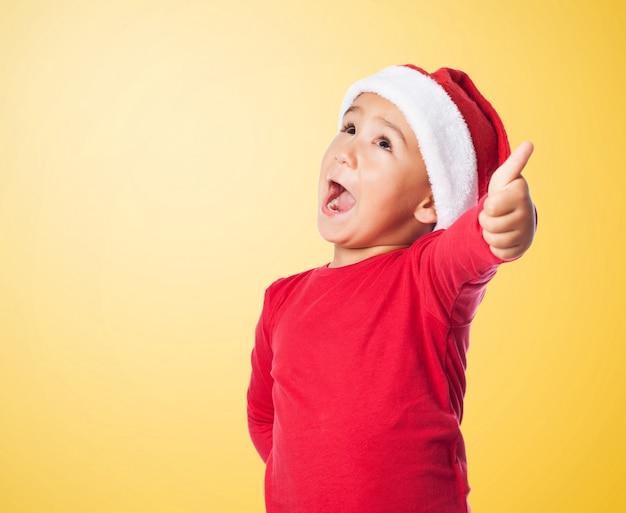 Bambino con il cappello e il pollice di santa up