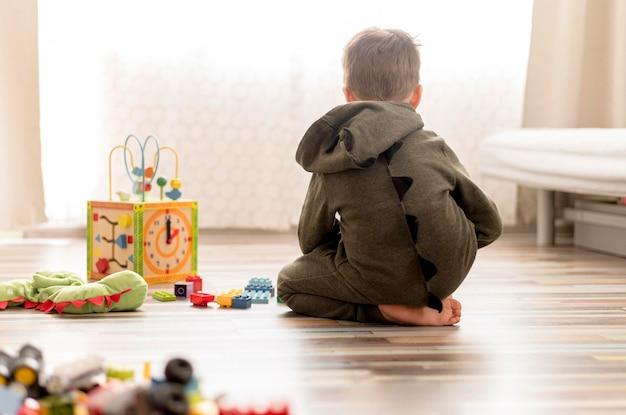 Bambino con il costume che gioca a casa