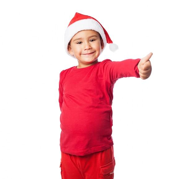 Bambino con il pollice alto e vestito rosso