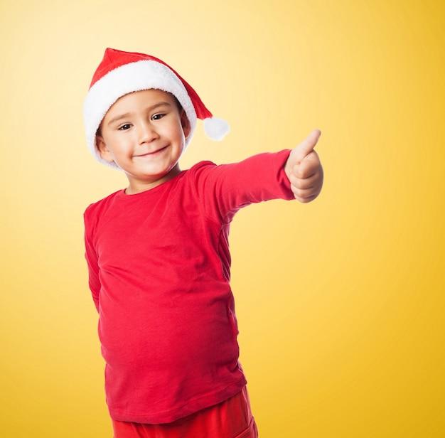Bambino con il pollice alto ed il cappello di babbo natale