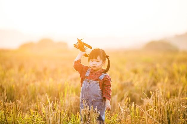 Bambino con l'aeroplano giocattolo in natura al tramonto