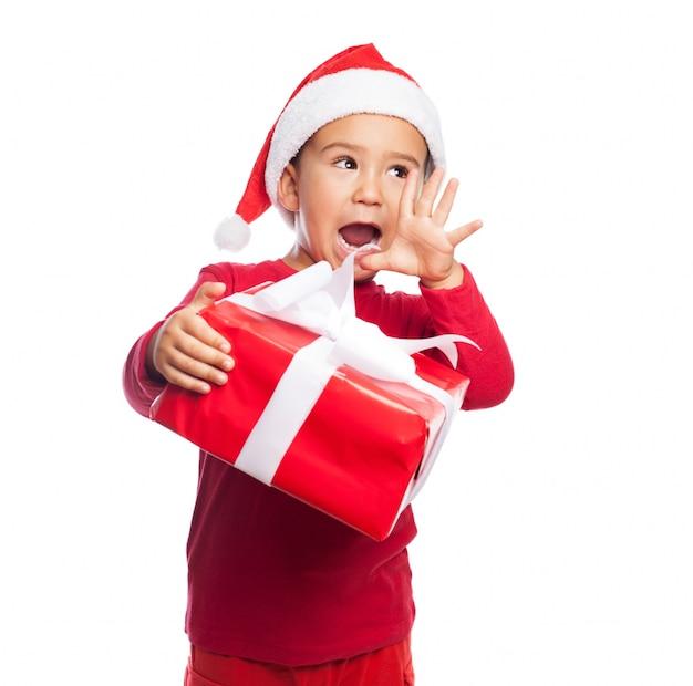 Bambino con la bocca aperta in possesso di un regalo