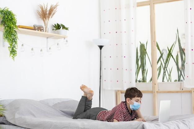 Bambino con la mascherina medica che guarda qualcosa sul computer portatile a letto