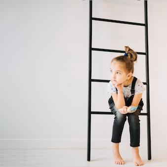 Bambino con la spazzola che si siede sulla scala vicino alla parete nella sala