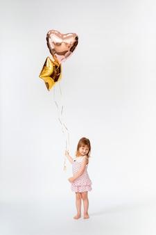 Bambino con palloncini a forma di cuore e stelle su bianco
