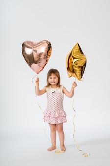 Bambino con palloncini a forma di cuore e stelle